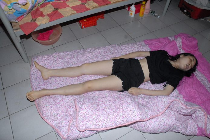 The corpse of a Chinese woman with an open mouth on a blanket