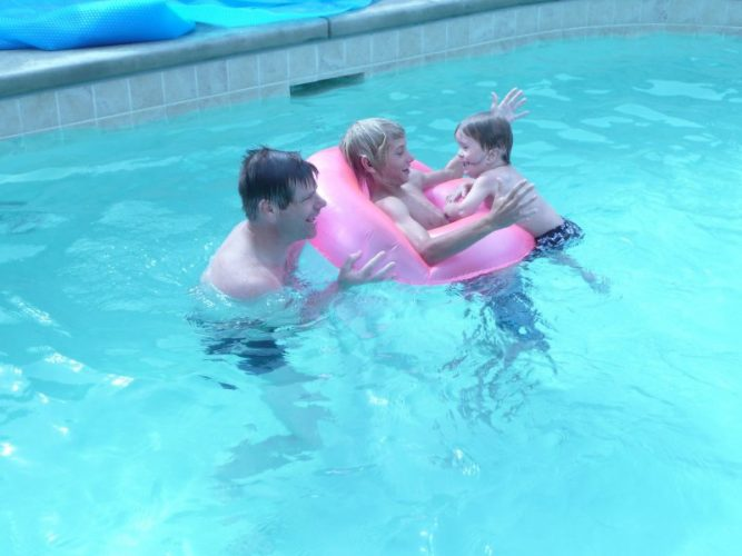 Denis with his family in the pool
